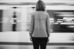 grayscale photo of woman in front of train